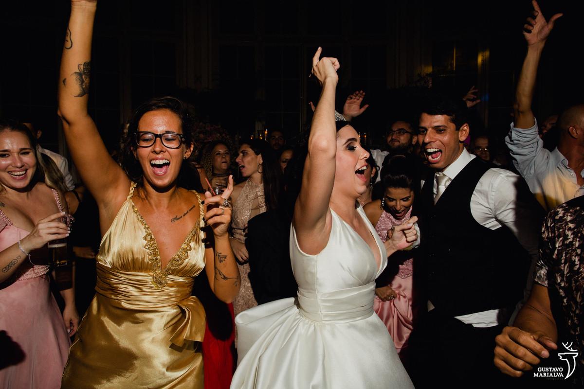 noivos pulando de alegria enquanto convidada dança segurando espumante
