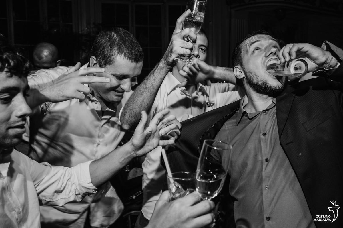 convidado coloca o copo inteiro de cerveja dentro da boca e outros amigos riem e dançam