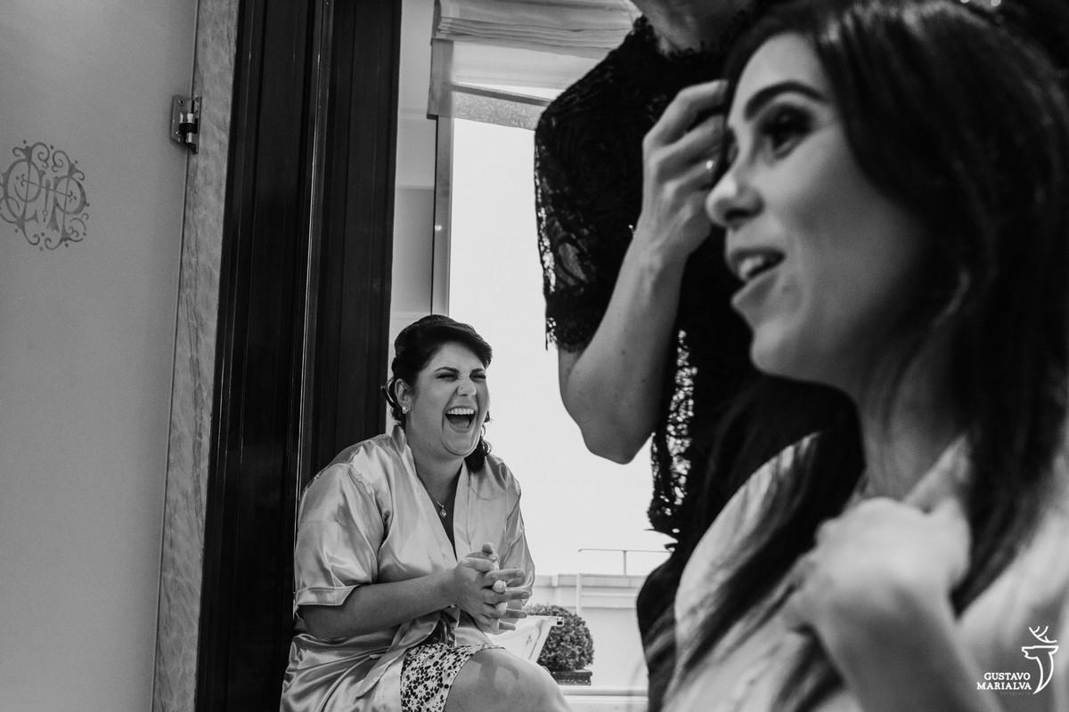 madrinha sorrindo com a noiva contando história engraçada