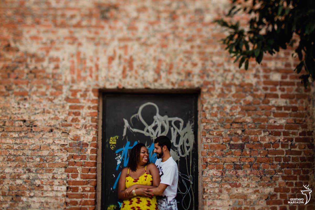 casal abraçando em frente ao porta pixada e parede de tijolos