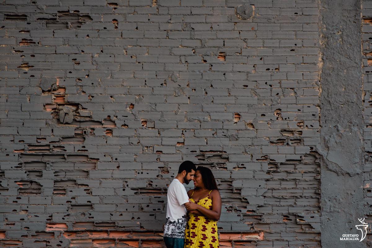 casal se abraçando em frente a parede de tijolos