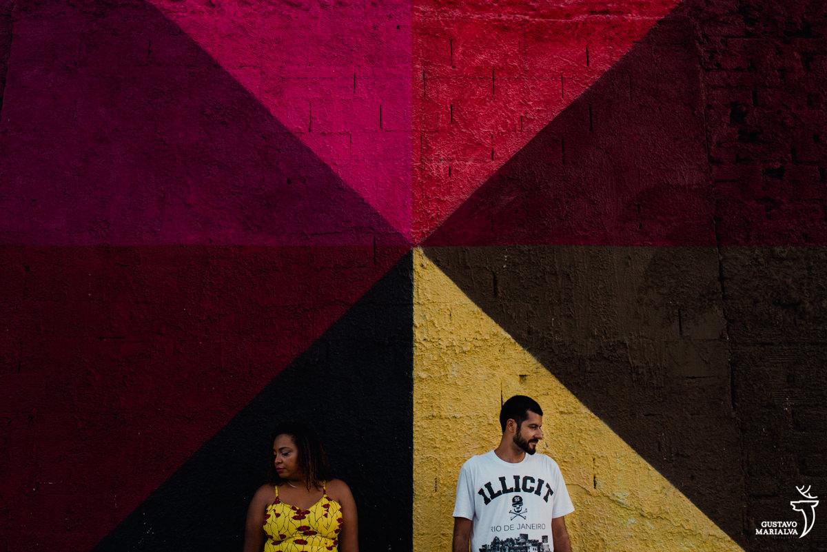casal posando durante book de casal em frente a painel do Kobra