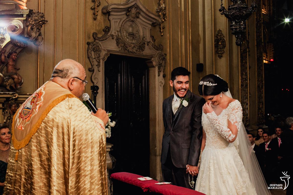 noivos sorrindo e padre celebrando a missa
