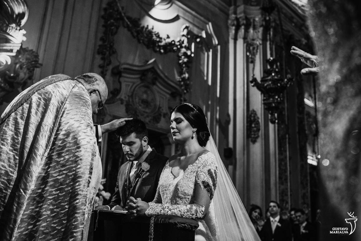 noivo sendo abençoado pelo padre enquanto noiva reza emocionada