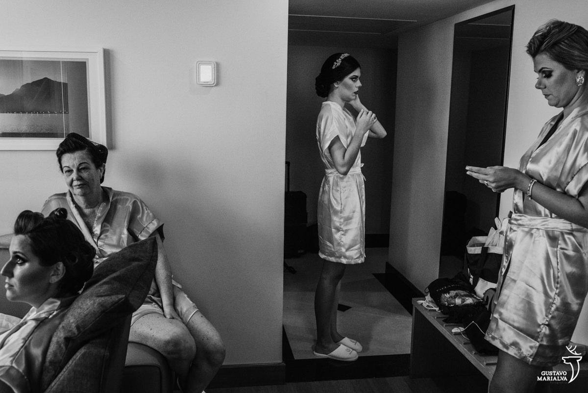 noiva se arrumando no espelho, madrinha olhando o celular e mãe da noiva e prima conversando