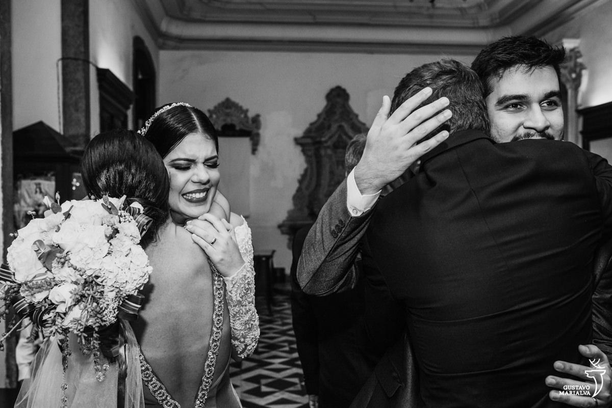 noiva emocionada abraçando a madrinha enquanto noivo abraça o padrinho