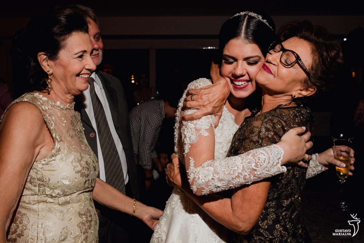 tia da noiva abraçando com carinho enquanto padrinhos observam