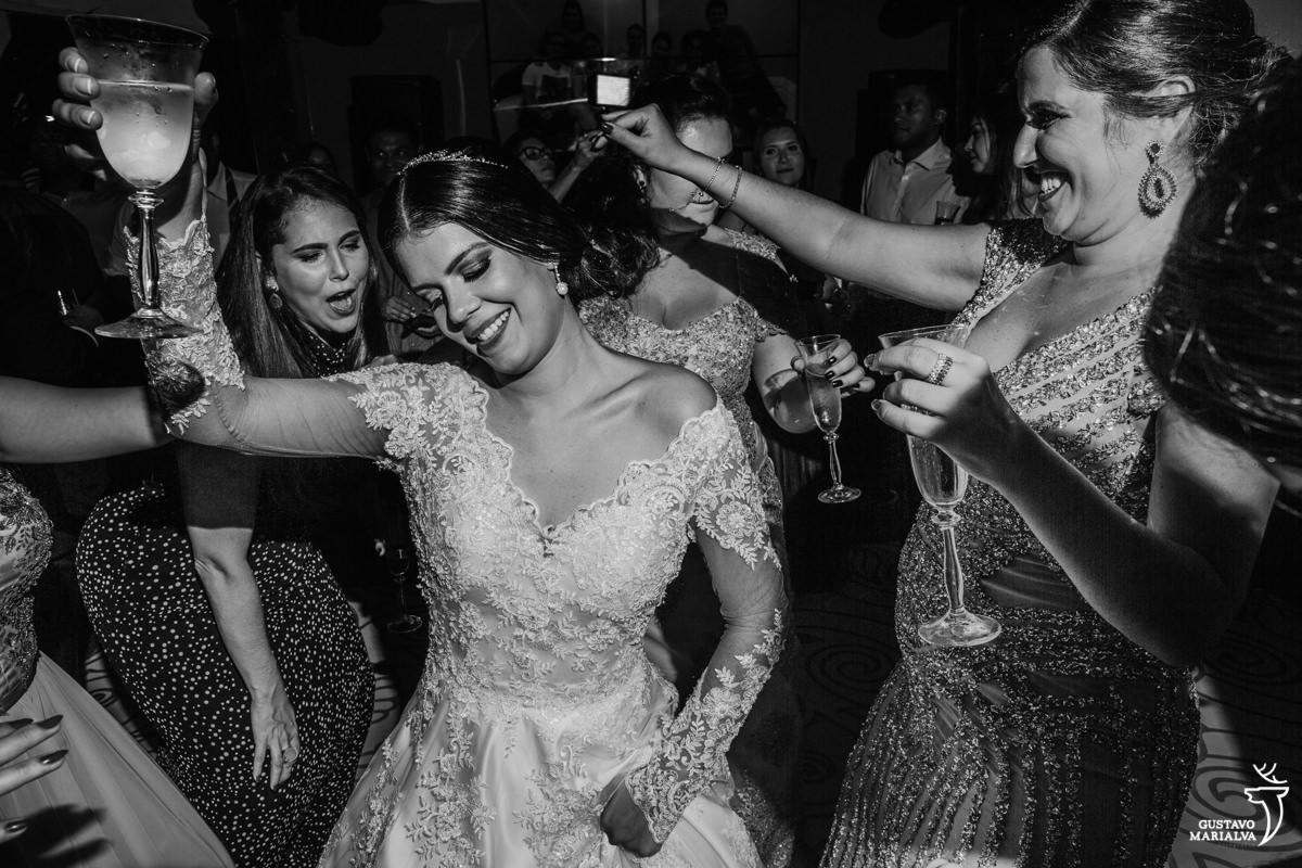 noiva, madrinha e amigas dançando funk segurando uma taça de espumante