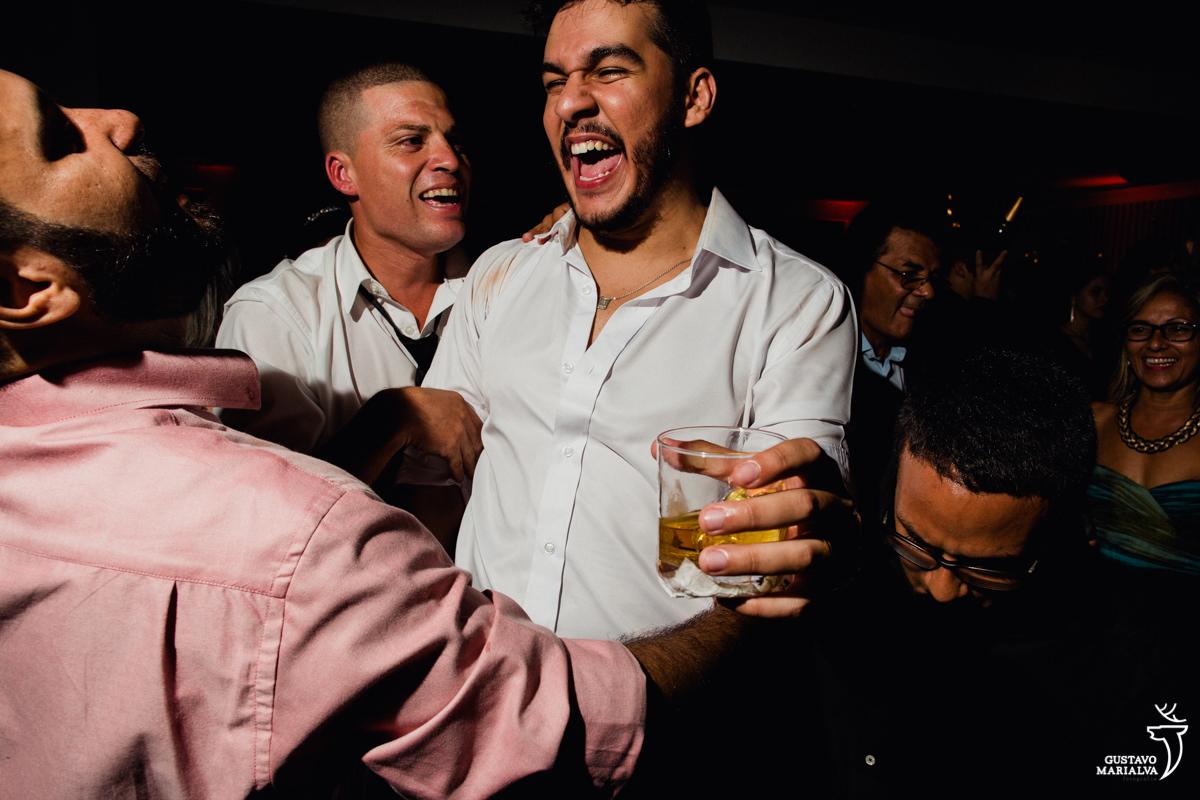 noivo segurando whisky e dançando com amigos