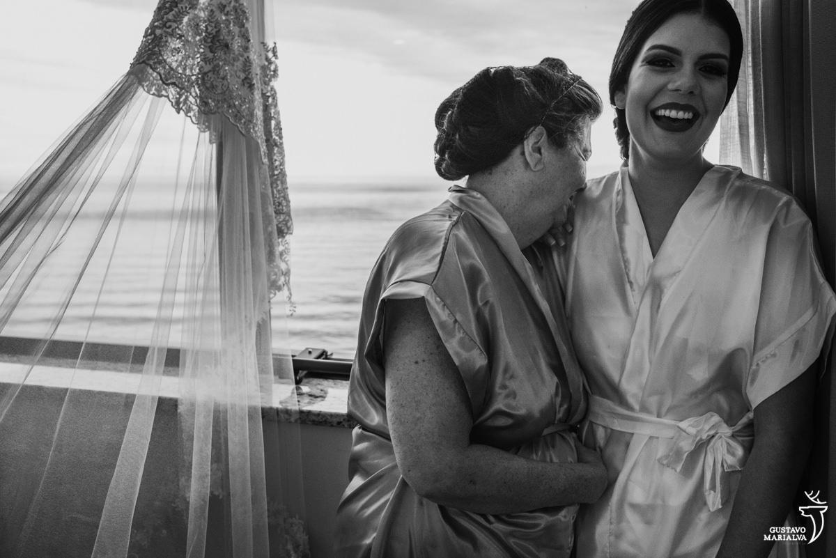 Noiva e mãe sorrindo emocionadas com a praia de copacabana de fundo