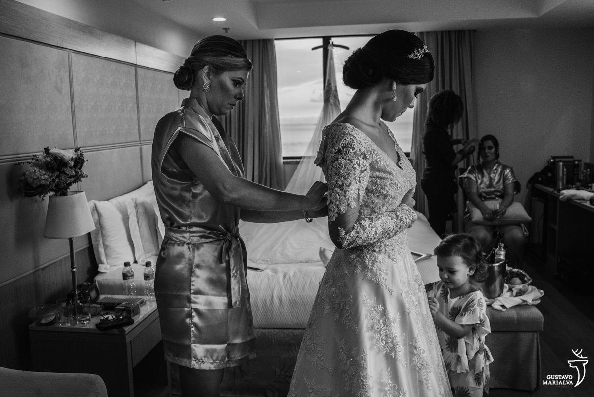 madrinha fechando o vestido da noiva e afilhada brincando com seu véu