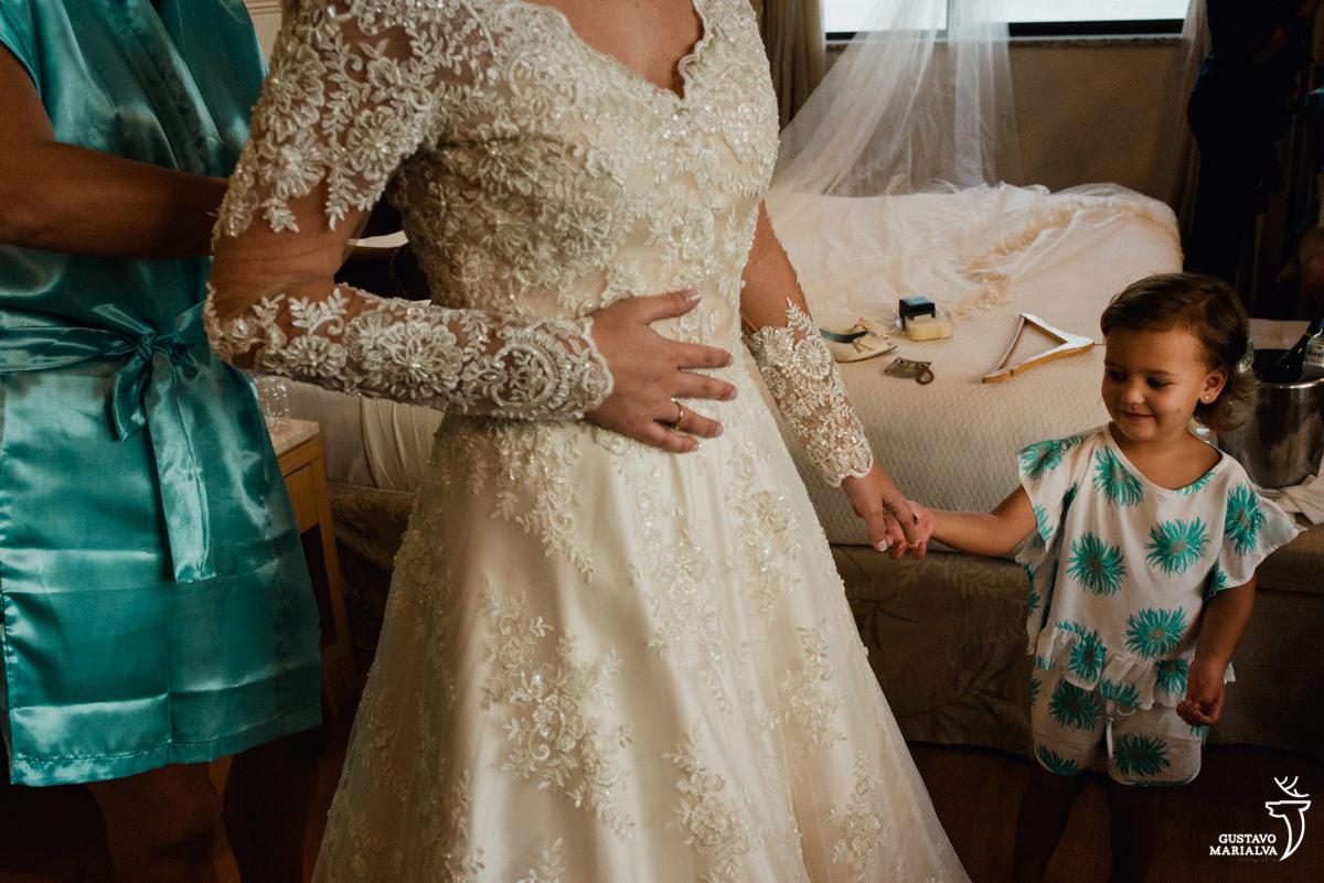 noiva segurando a mãe da afilhada enquanto a madrinha fecha o vestido