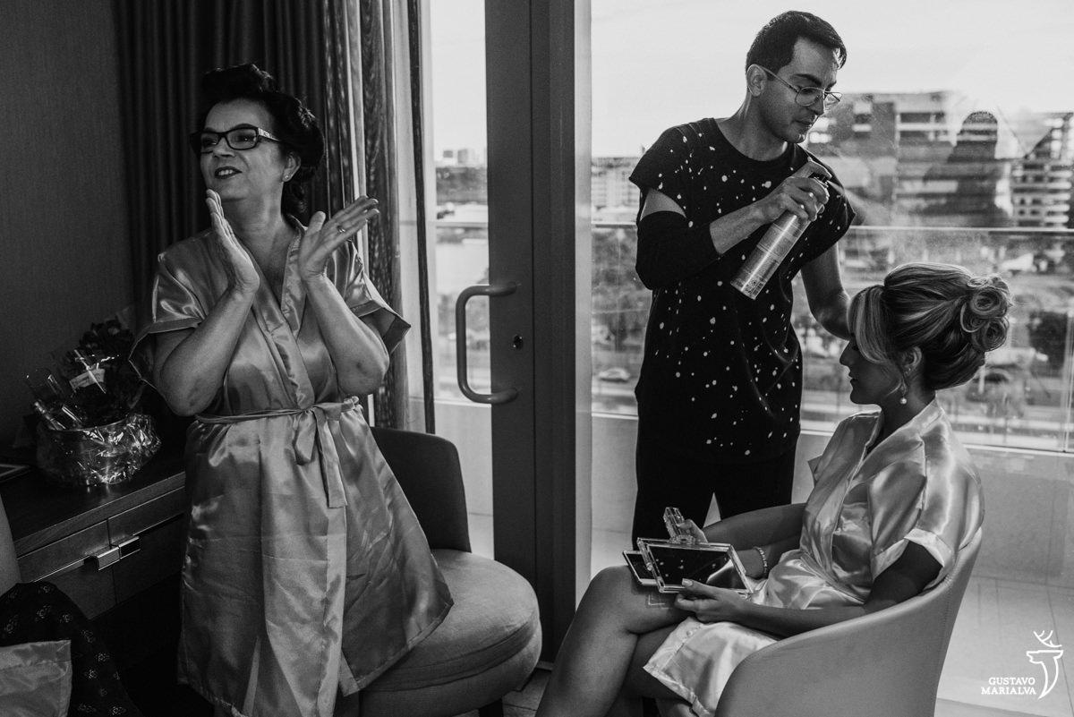 mãe da noiva aplaudindo enquanto a noiva arruma o cabelo com o maquiador daniel wagner no making of do casamento no hotel hilton no rio de janeiro