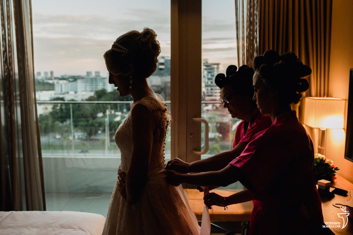 madrinha e mãe da noiva fechando o vestido de casamento da noiva no making of do casamento no hotel hilton no rio de janeiro