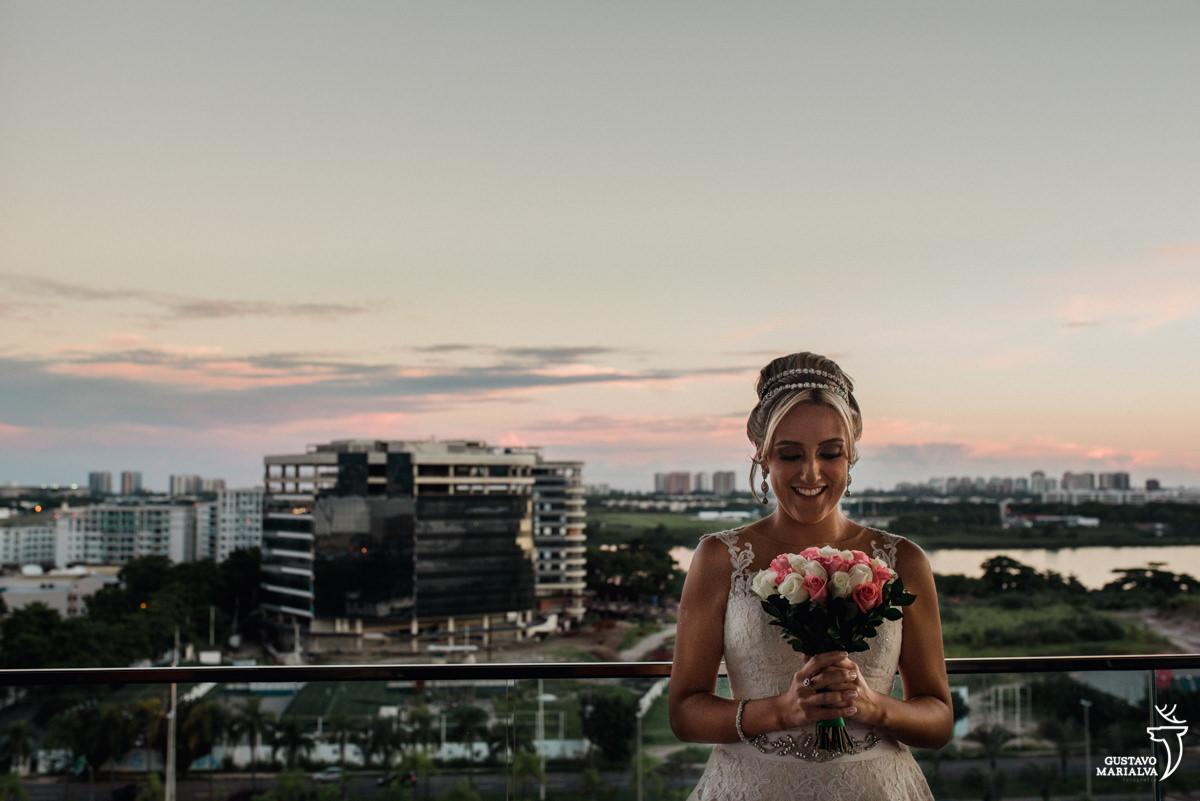 noiva segurando o buque e sorrindo com a barra da tijuca ao fundo, no por do sol, durante o making of do casamento no hotel hilton no rio de janeiro