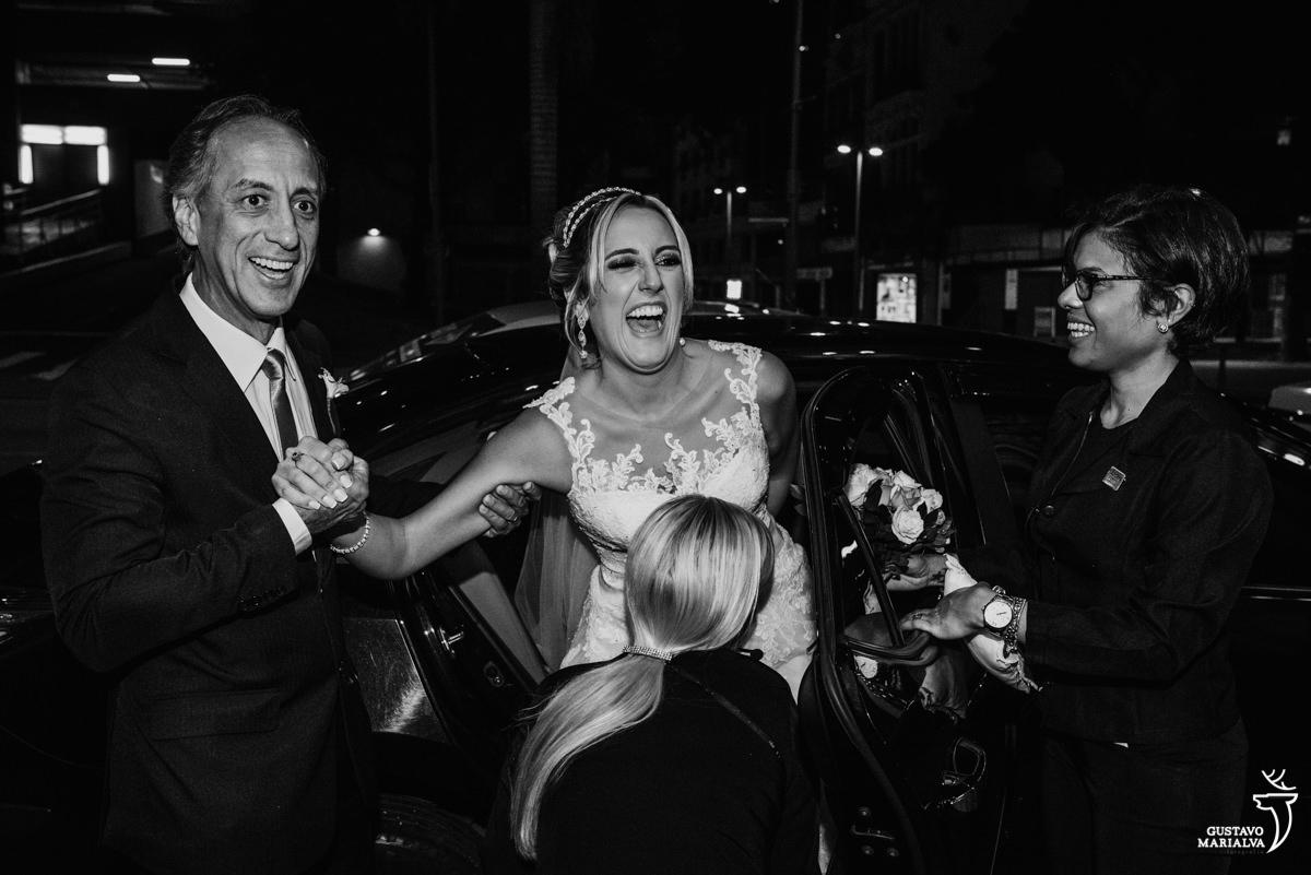 noiva sorrindo muito ao sair do carro ajudada pelo pai e por duas cerimonialistas antes de começar a cerimônia de casamento na igreja são josé no rio de janeiro