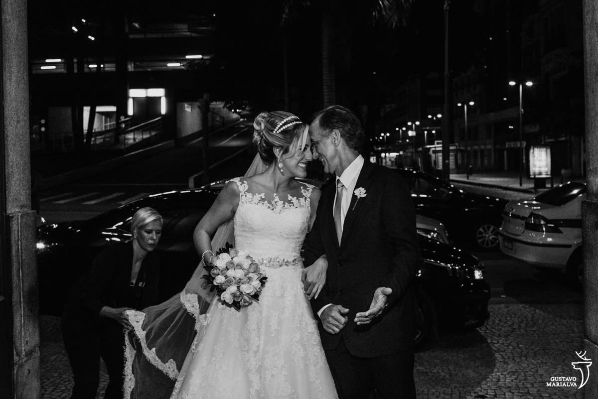 noiva e pai colando a testa e sorrindo antes de entrar na cerimônia de casamento na igreja são josé no rio de janeiro enquanto a cerimonialista arruma o vestido