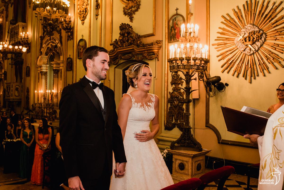 noiva e noivo sorrindo, enquanto a noiva coloca a mão na barriga, na cerimônia de casamento na igreja são josé no rio de janeiro