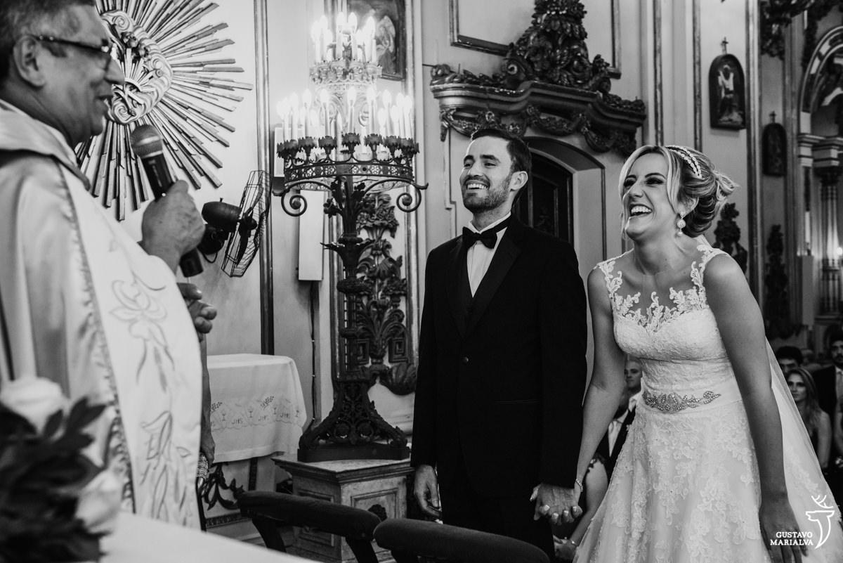 noivos sorrindo de mãos dadas enquanto escutam a missa do padre na cerimônia de casamento na igreja são josé no rio de janeiro