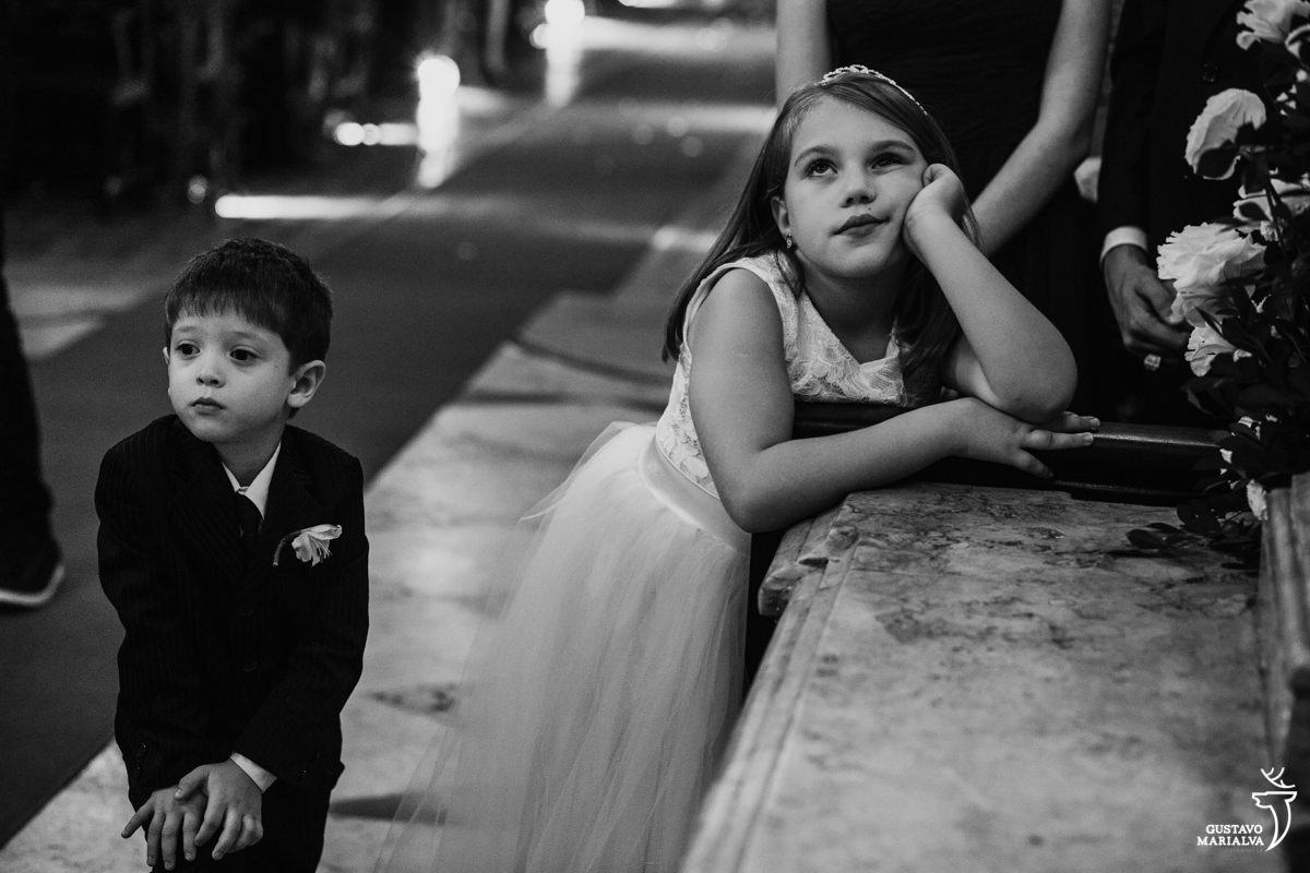 daminha apoiando a mão no rosto com sono enquanto pajem presta atenção na cerimônia de casamento na igreja são josé no rio de janeiro