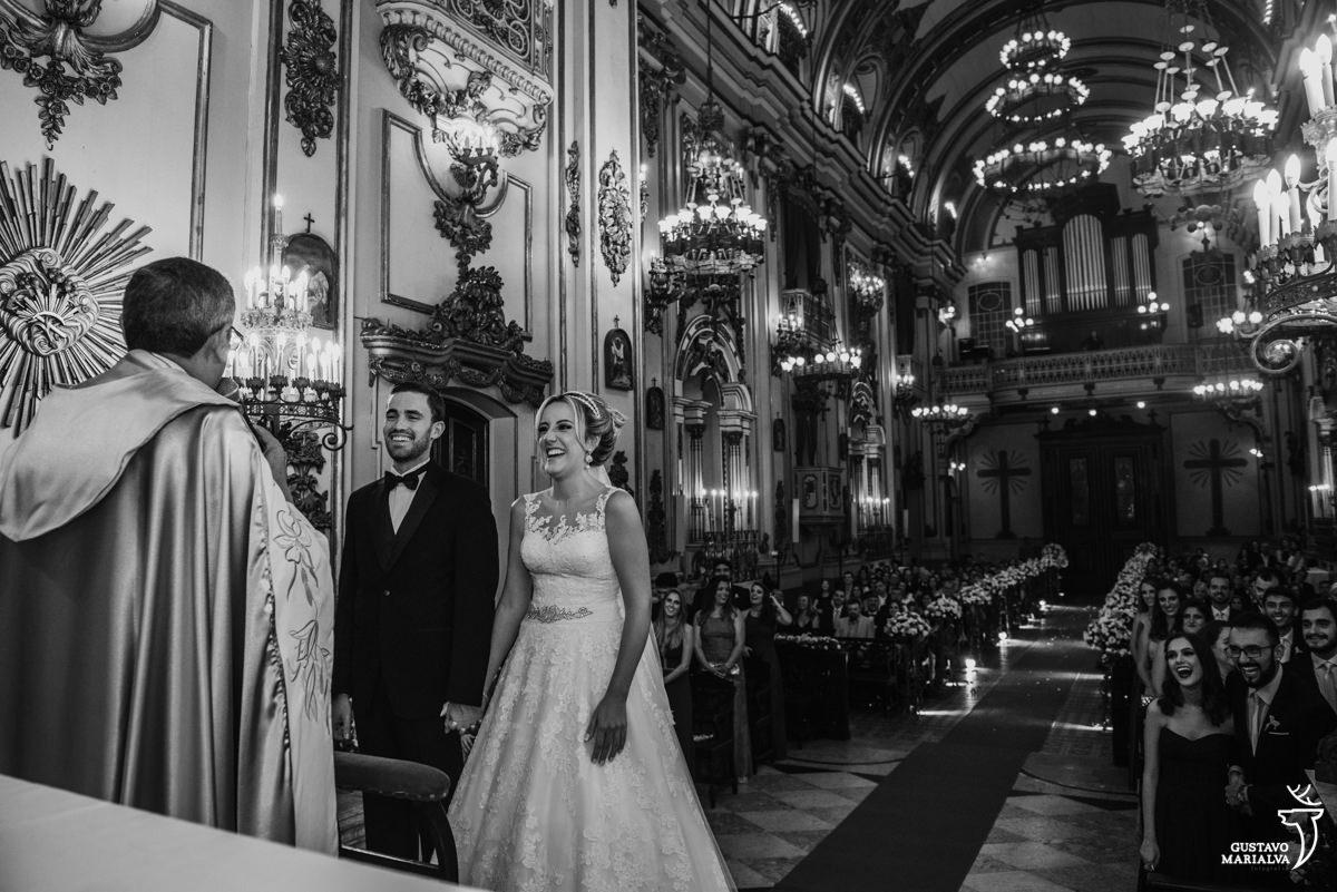 noivos sorrindo enquanto escutam o padre falar e convidados sorrindo ao fundo durante a cerimônia de casamento na igreja são josé no rio de janeiro