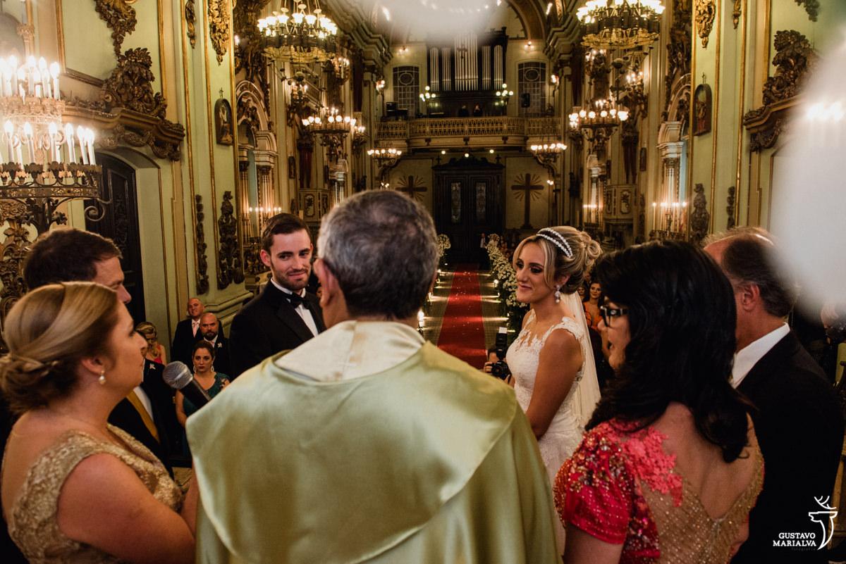 noivos observam a mãe do noivo, emocionada, discursar com os pais dos noivos durante a cerimônia de casamento na igreja são josé no centro do rio de janeiro