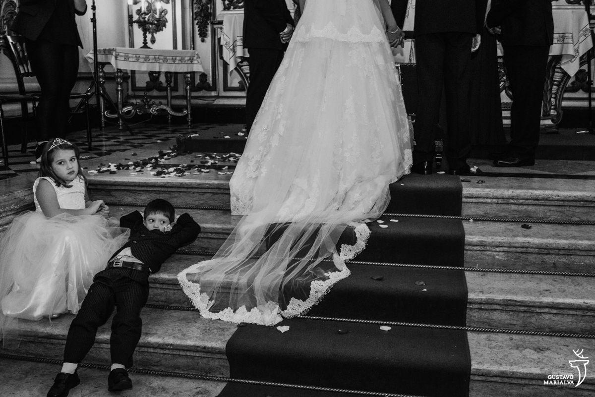 pajem deitado na escada do altar, com a daminha sorrindo enquanto os noivos observam o padre falar durante a cerimônia de casamento na igreja são josé no rio de janeiro