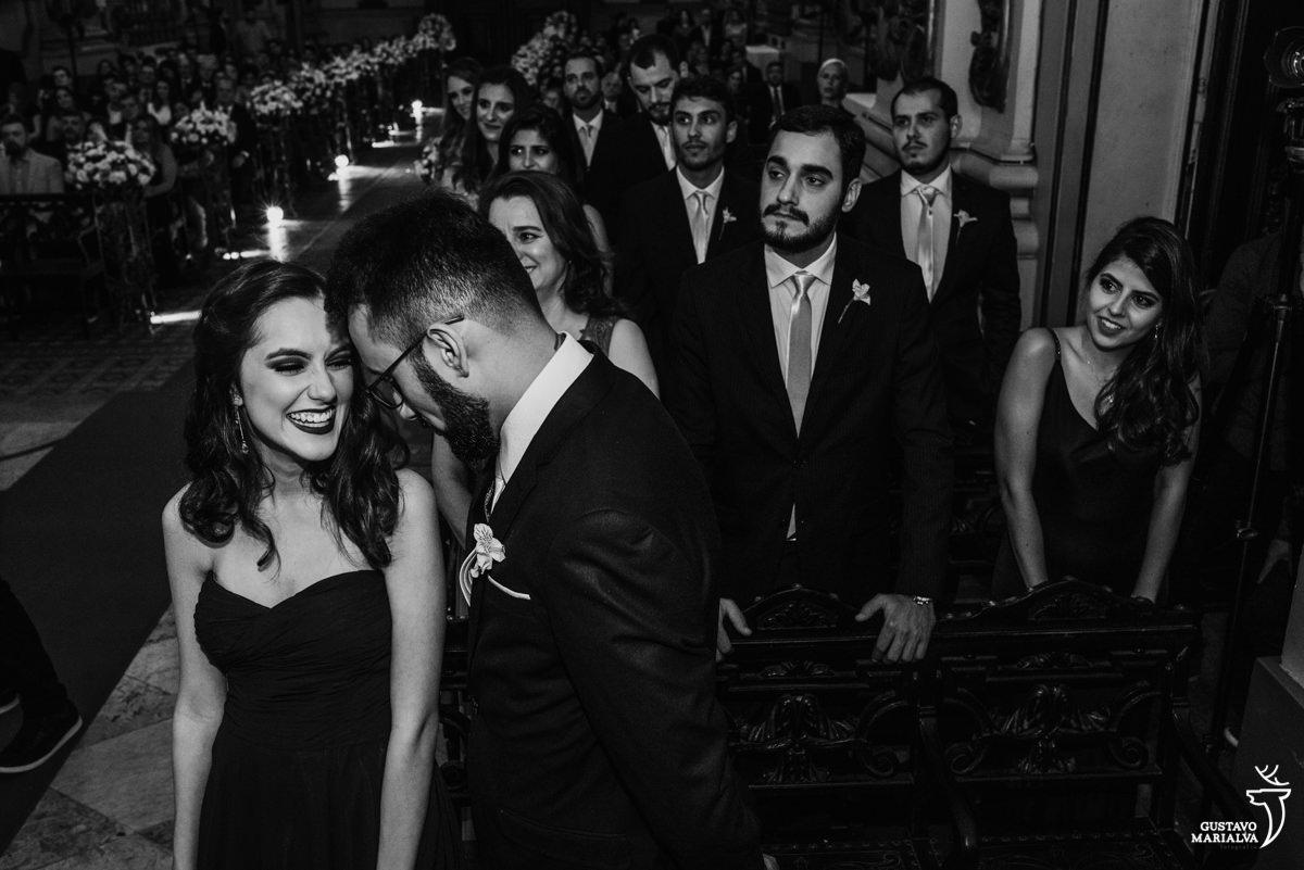 irmã da noiva e padrinhos sorriem emocionados, com padrinhos ao fundo, durante a cerimônia de casamento na igreja são jose no rio de janeiro