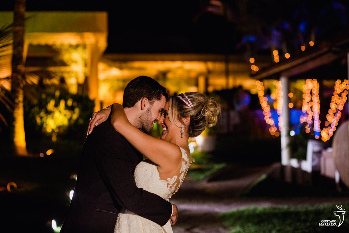 noivos sorriem abraçados com o clube mandala ao fundo