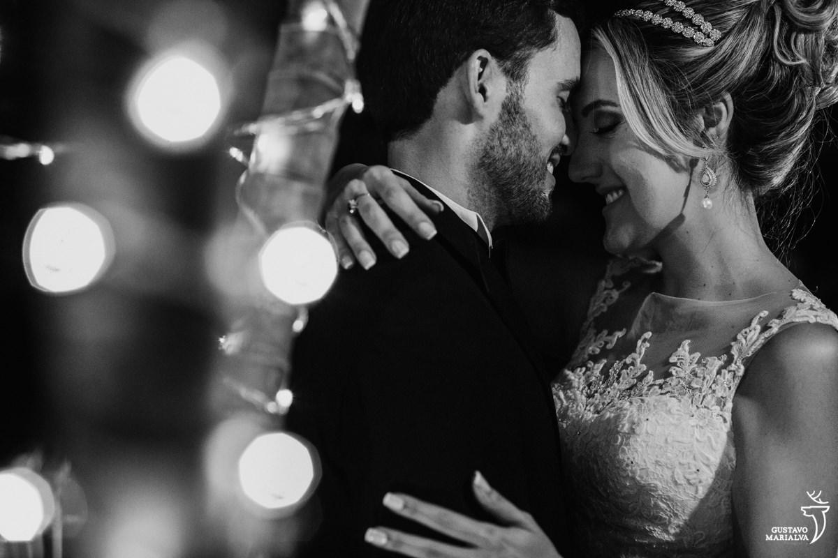 noivos sorriem e se abraçam carinhosamente com luzes de natal desfocadas enfeitando a foto