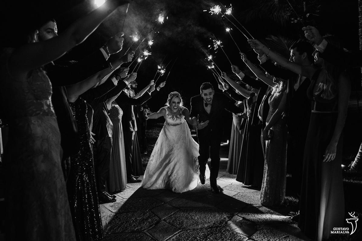 padrinhos fazem corredor de sparkles para que os noivos entrem na festa de casamento no clube mandala no rio de janeiro