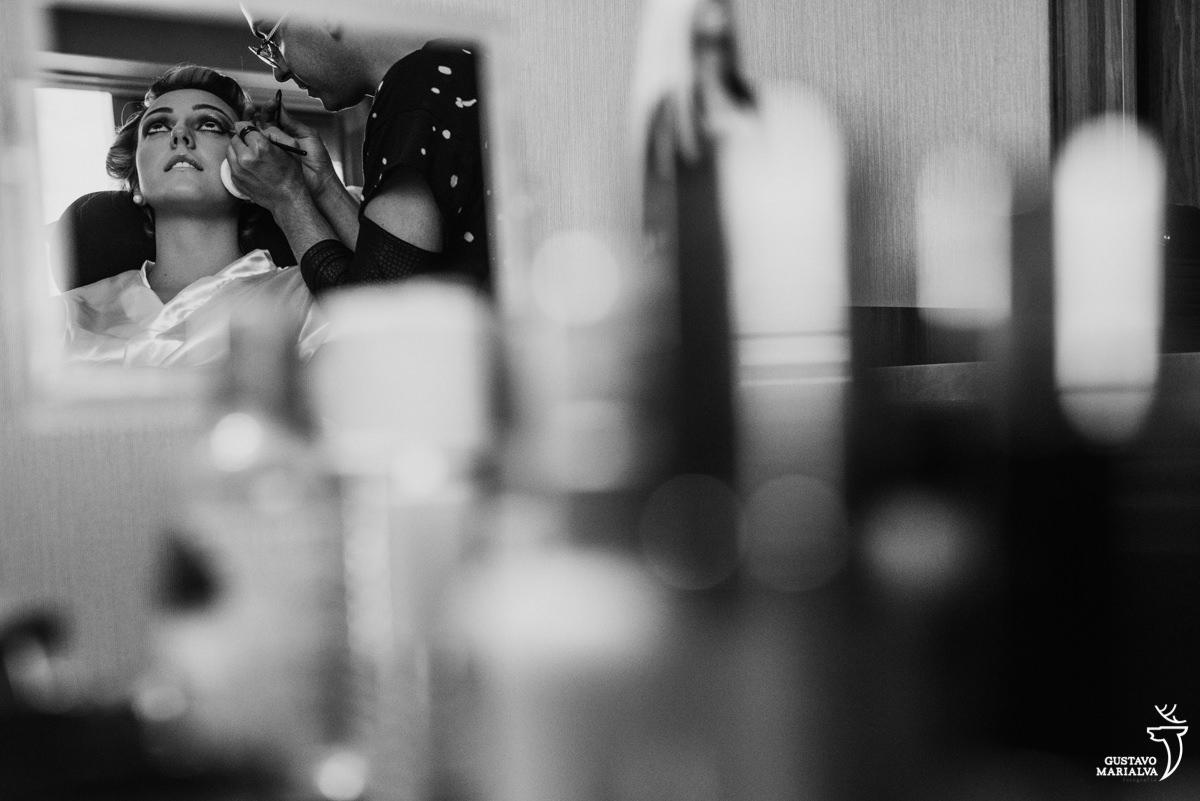 noiva sendo maquiada e fotografada no reflexo do espelho no making of do casamento no hotel hilton no rio de janeiro