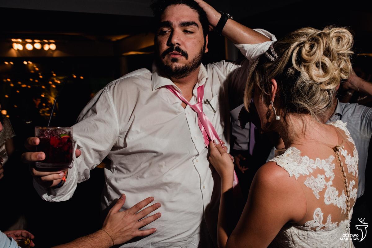 convidado faz cara sensual enquanto a noiva puxa sua gravata na festa de casamento no clube mandala