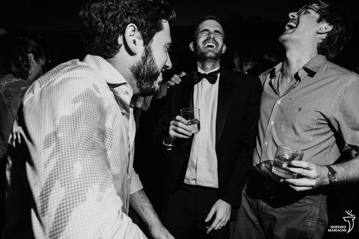 noivo sorri e dança de olhos fechados acompanhado dos amigos
