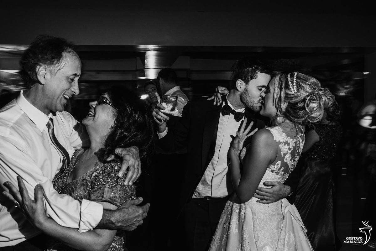 noivos se beijam e pais da noiva dançam emocionados
