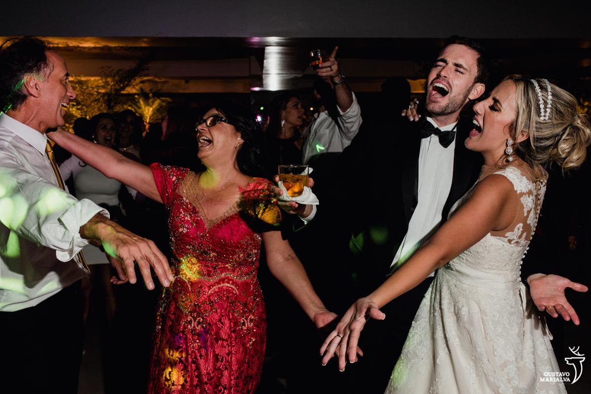 pais da noiva e noivos dançam e gritam comemorando o casamento