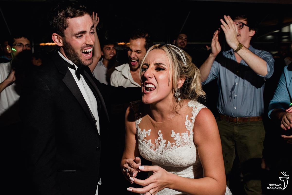 noivo e noiva dançam alegres com convidado batendo palmas no fundo e outro gritando