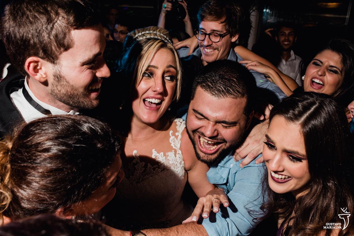 convidados abraçam os noivos sorridentes