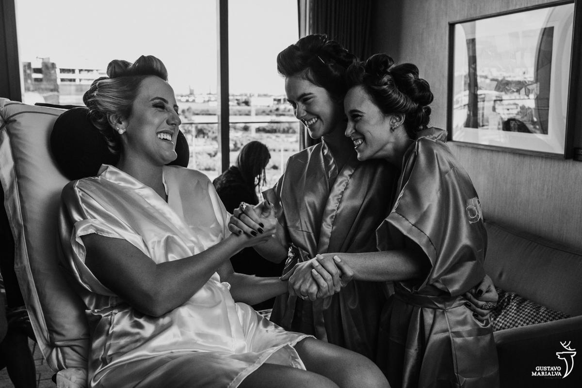 noiva segurando a mão da irmã e madrinha, sorrindo enquanto elas se abraçam no making of do casamento no hotel hilton no rio de janeiro