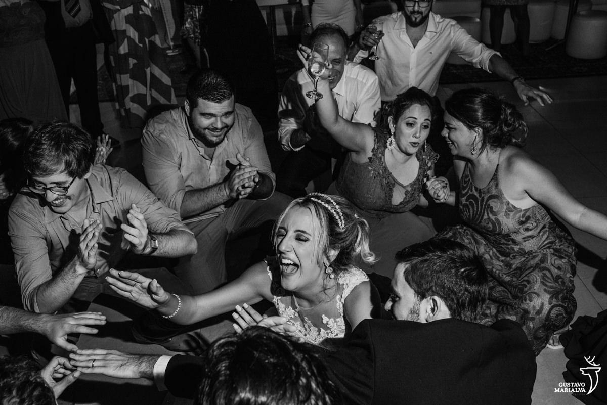 noivos dançam com amigos agachados no chão, gritando e sorrindo
