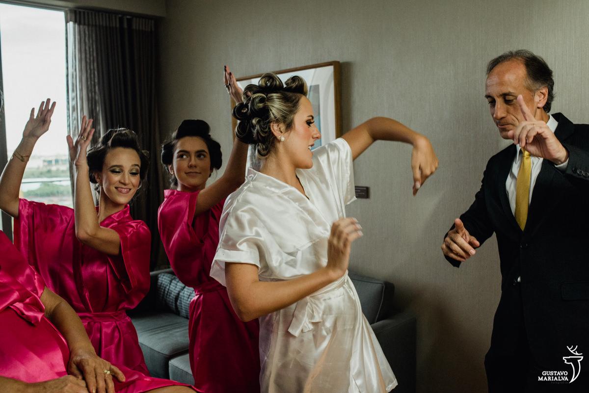 noiva, irmã, madrinha e pai dançando e sorrindo durante o making of do casamento no hotel hilton no rio de janeiro