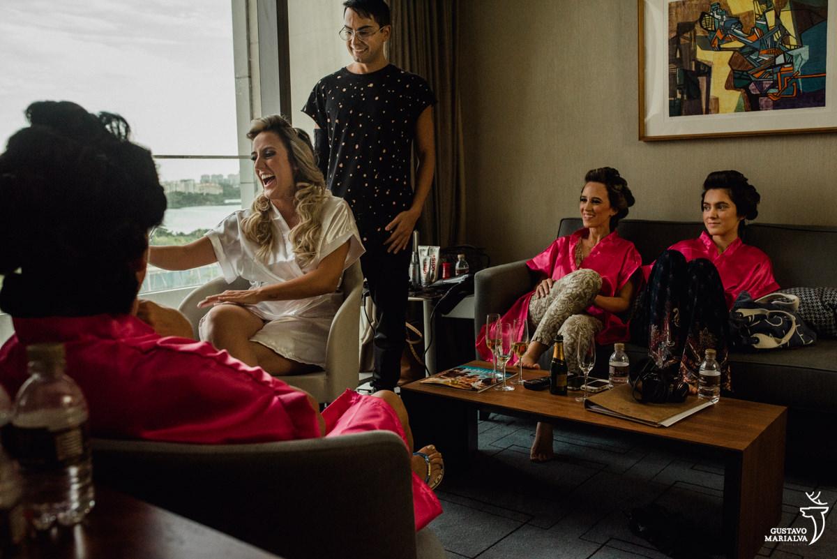 mãe observando a noiva sorrir enquanto o maquiador daniel wagner arruma o seu cabelo e irmã e madrinha sorrindo ao fundo no making of do casamento no hotel hilton no rio de janeiro