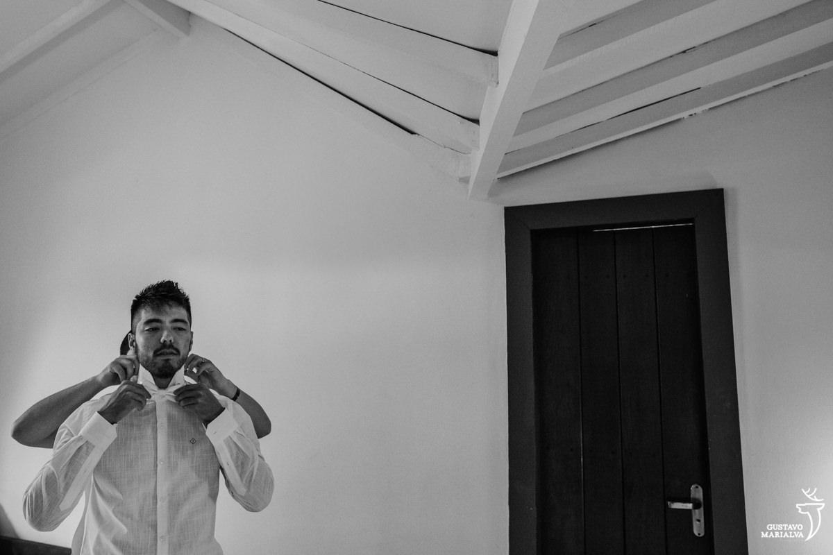 padrinho ajuda o noivo a colocar a gravata borboleta