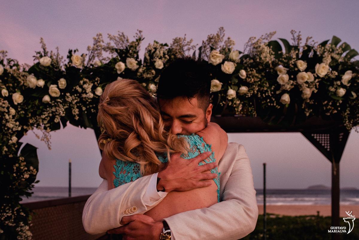 noivo abraça a mãe na entrada da cerimônia de casamento no Uniq Beach Lounge em Búzios