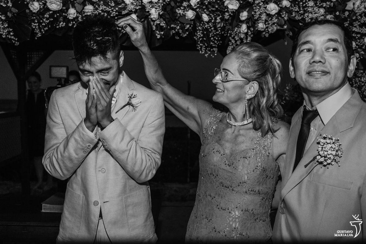 Noivo chora emocionado com a mão no rosto ao ver a noiva entrar enquanto os pais fazem carinho nele no Uniq Beach Lounge em Búzios