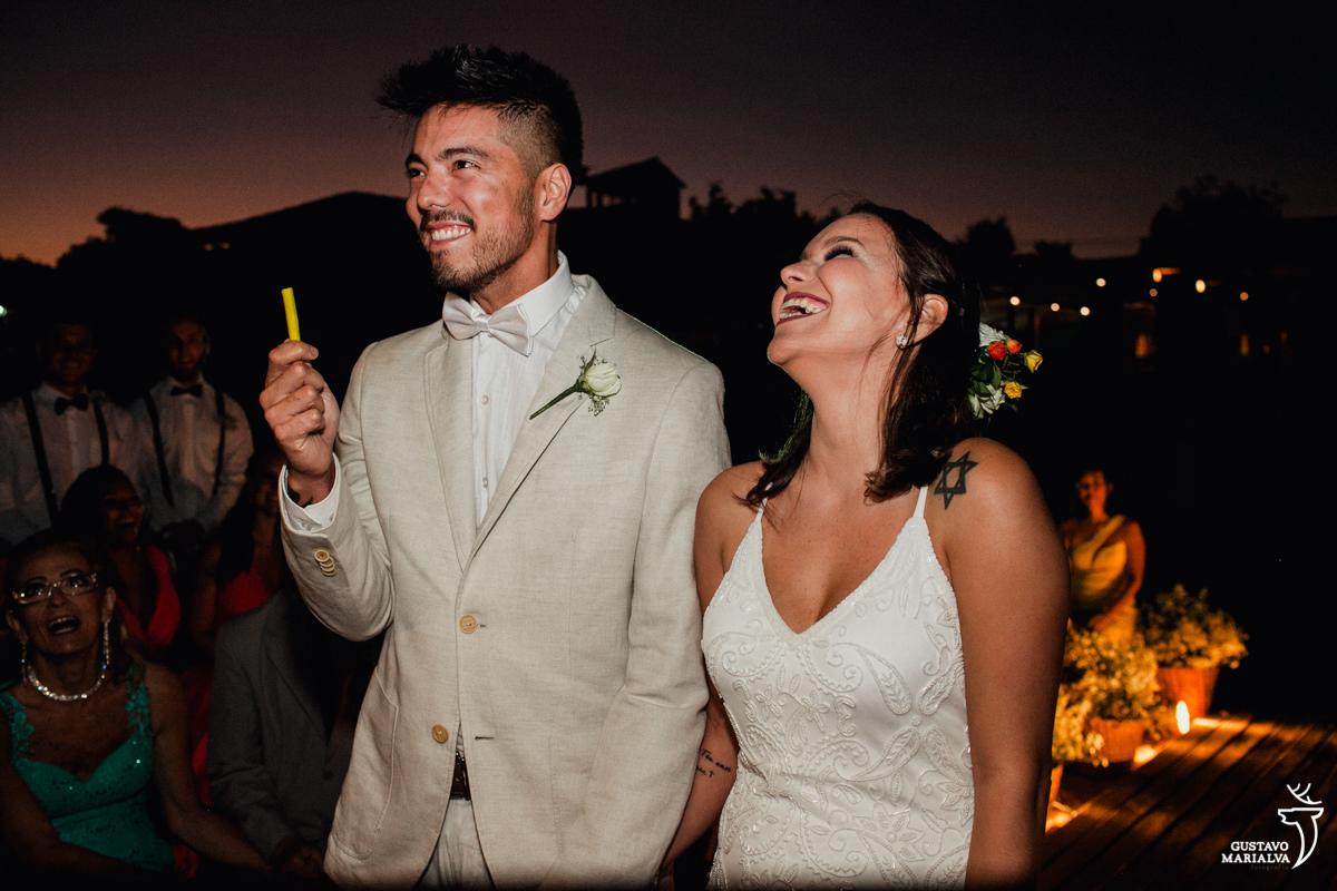 Noivo segurando massinha amarela e sorrindo enquanto a noiva sorri na cerimônia de casamento no Uniq Beach Lounge em Búzios