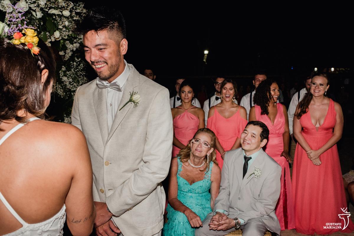noivo sorri emocionado com os pais e madrinhas ao fundo emocionadas na cerimônia de casamento no Uniq Beach Lounge em Búzios