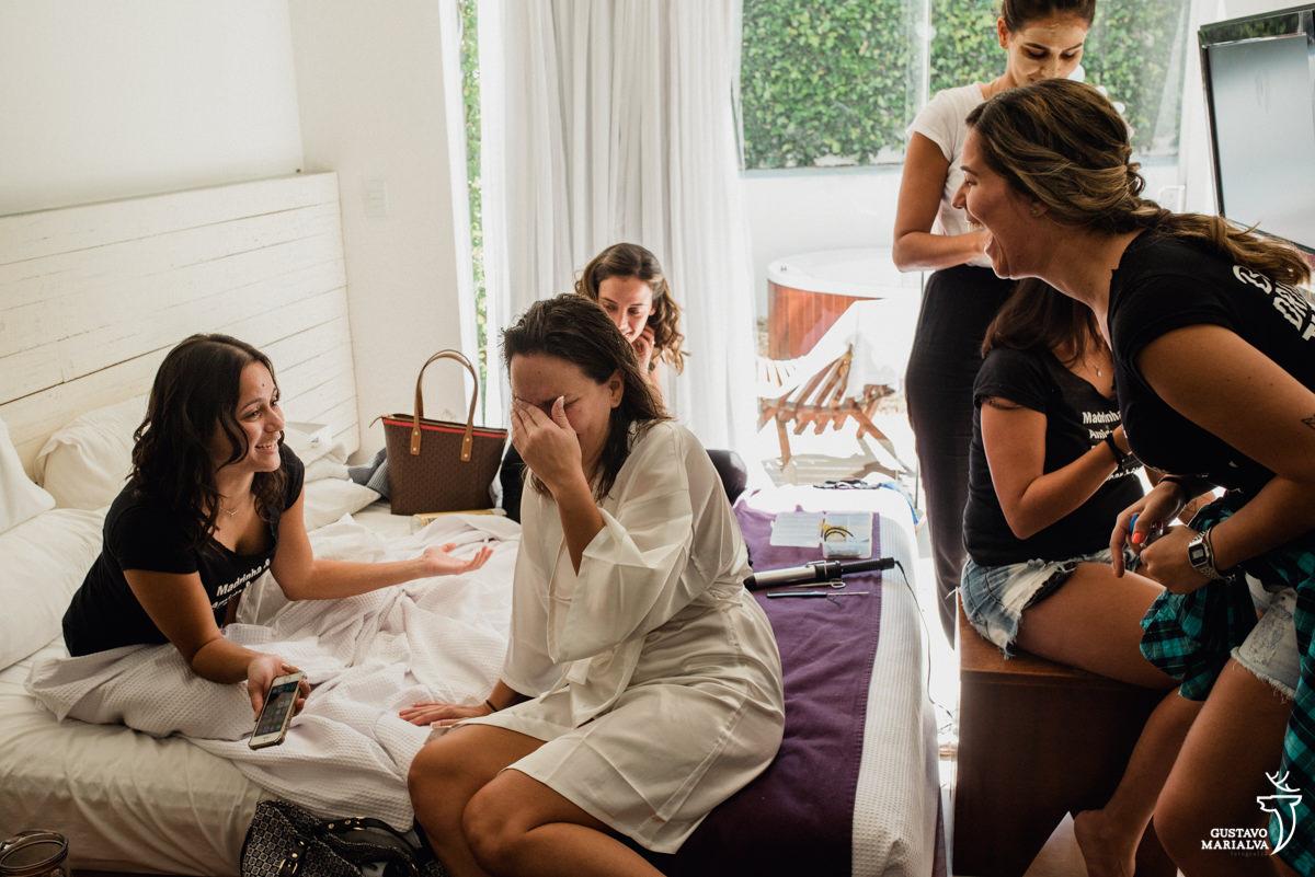 madrinhas zoam a noiva que ri bastante com a mão no rosto durante o making of do casamento na Serana Boutique Resort em Búzios