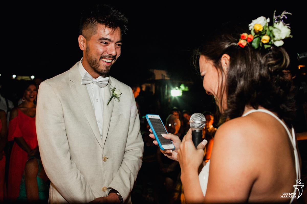 noivo sorri emocionado enquanto a noiva le os votos no celular durante a cerimônia de casamento no Uniq Beach Lounge em Búzios