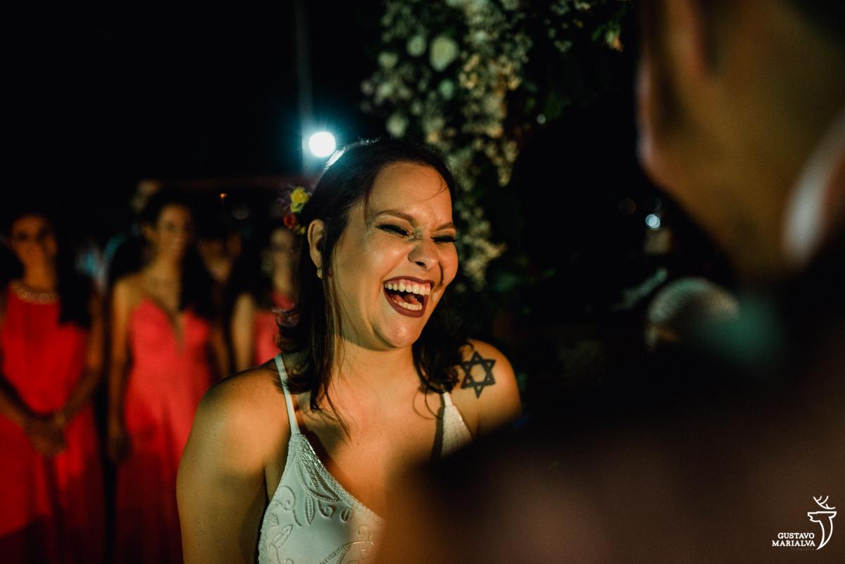 noiva sorri emocionada com as madrinhas ao fundo enquanto o noivo lê os votos na cerimônia de casamento no Uniq Beach Lounge em Búzios
